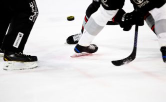 hockey players puck in air